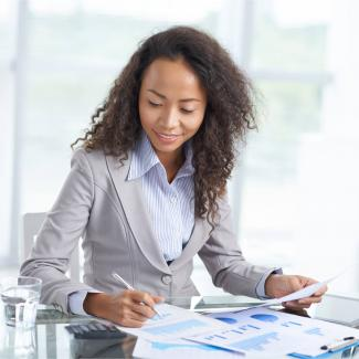 Young woman in business attire sitting at desk reviewing financial documents.