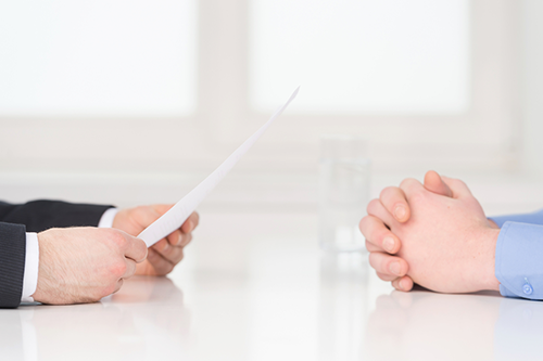 A candidates hands holding a list of interview questions across from an employers clasped hands