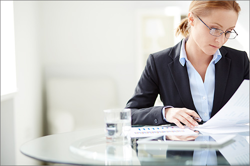 A woman working at a table looking at a report