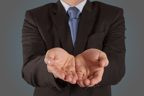 An accountant extends his hands forward, palms up, to illustrate salary negotiation