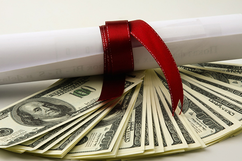 A stack of $100 bills are fanned out with a rolled-up accounting certificate on top