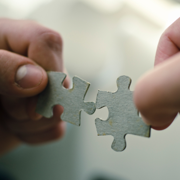 Two hands attempt to link two pieces of a puzzle