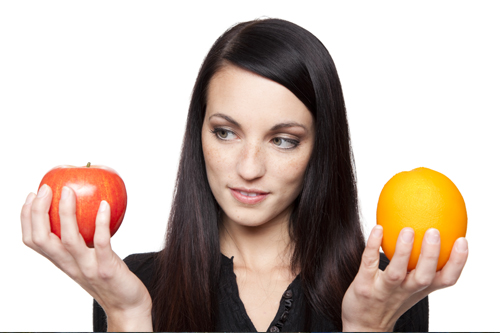 A woman holding an apple and an orange