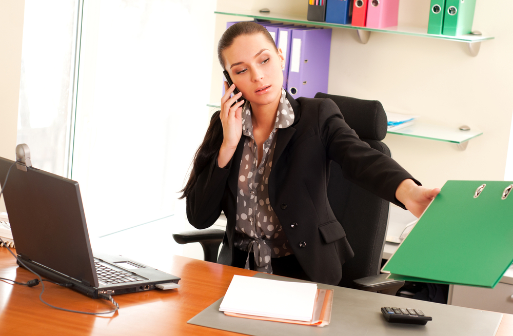 A finance professional discusses work on the phone at her desk