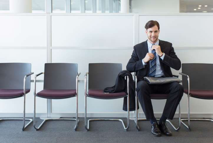 A candidate straightens his tie while waiting to be interviewed at a staffing firm