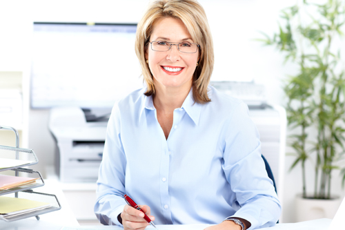 A smiling female senior accountant sits at a desk