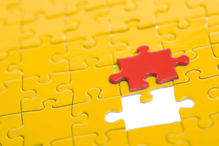 A puzzle has one piece left to assemble
