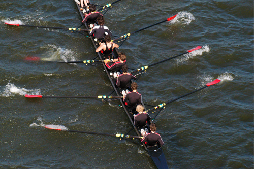 Rowers propel a racing shell across the water