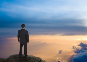 A man standing at a mountain precipice stares into the clouds