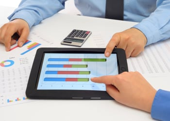 An iPad displaying an accounting graph with the hands of two accounting professionals pointing at the screen