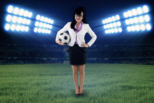A female accountant stands on a grass athletic field holding a soccer ball