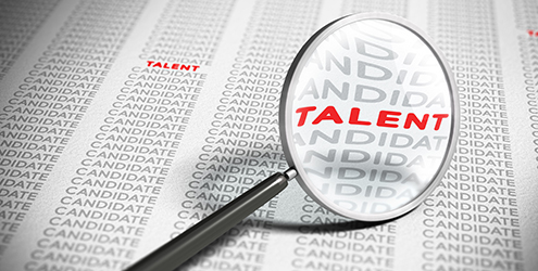 "A magnifying glass highlights the word ""Talent"" in a mass of candidates"