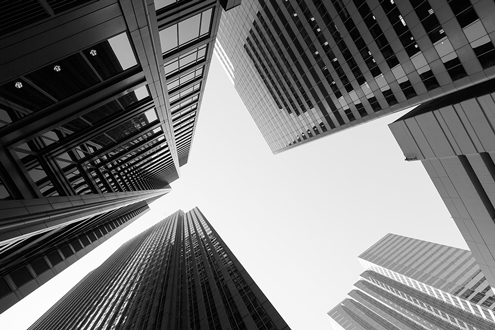 A view skyward from the ground comes from between large bank buildings
