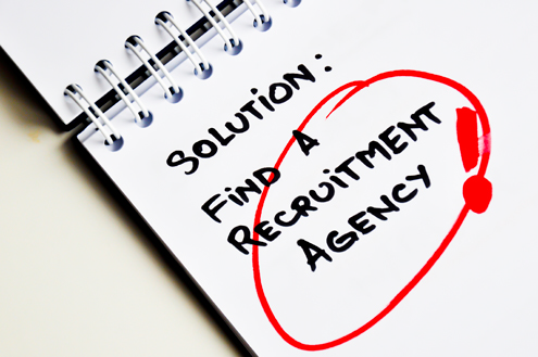 "A spiral notebook is open with the words ""Solution: Find a recruitment agency!"" circled on a page"