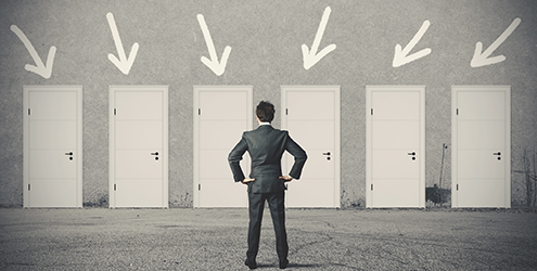 An entry level accountant stands in front of a series of doors with arrows pointing down on each one