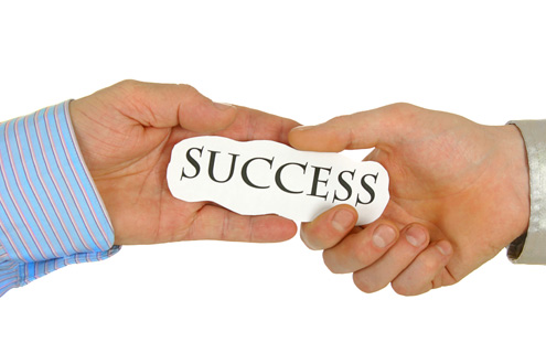 "A recruiter's hand passing the word ""Success"" to a candidate's hand"