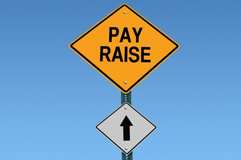 """A road sign has an arrow pointing up to another road sign that says """"Pay Raise"""""""
