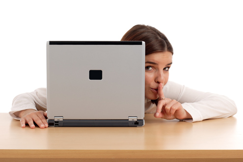 An employee looking for a new job peeks around her laptop with a finger to her lips