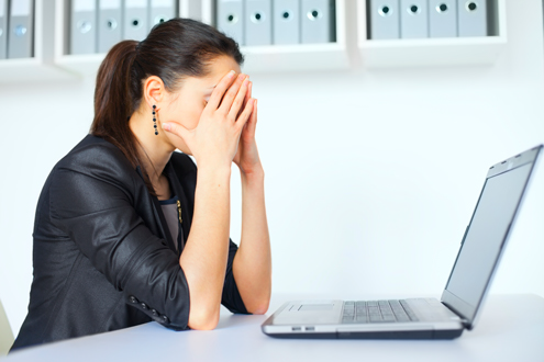 A manager with recruitment challenges covers her eyes while sitting at her laptop computer