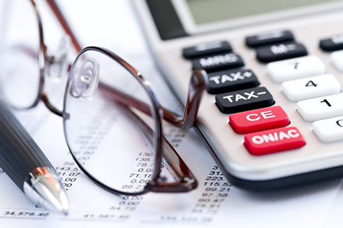 A pen, eyeglasses and a calculator lie on a bookkeeper's report