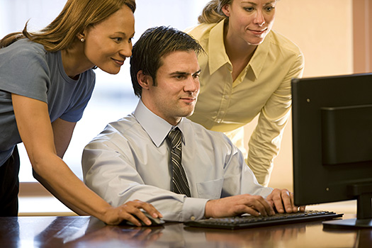 Two women and a man looking at consulting jobs on a computer