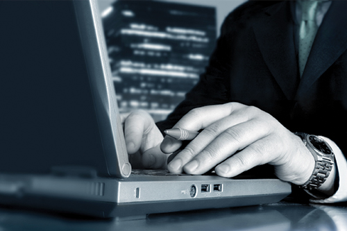 A mans hands typing on a laptop he is using to research consulting firms