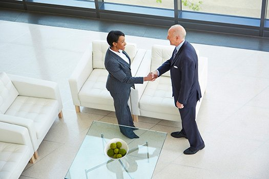 A candidate shakes hands with a recruiter after she decides to try working with a staffing agency