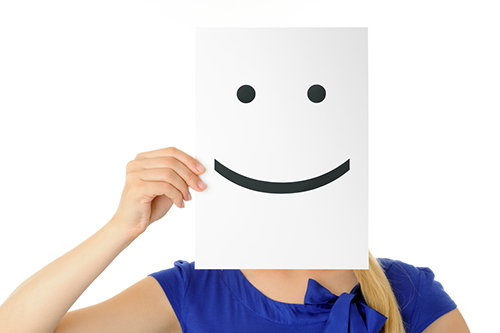 A woman holds a sheet of paper with a smiley face in front of her own face