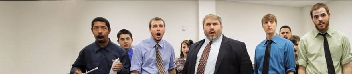 Office workers stand in an office looking surprised