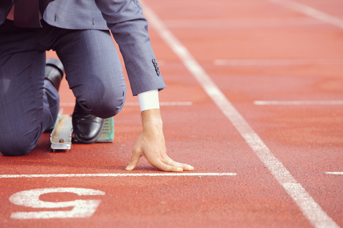A partial image of a man in a suit crouching in a starting lane before a race
