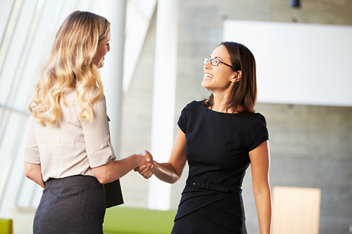 A hiring manager congratulating a candidate for landing an administrative assistant job