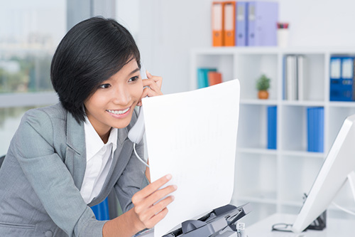A femle administrative assistant is smiling on the phone and looking at a document