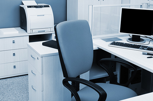An office cubicle has an empty chair