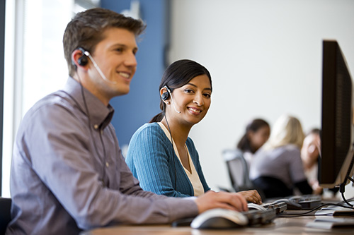 A smiling man and woman working at a call center with colleagues in the background