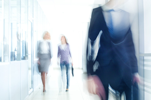 A blurred image of administrative professionals arriving for work