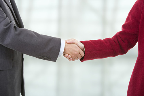 A partial image of people shaking hands at a staffing firm