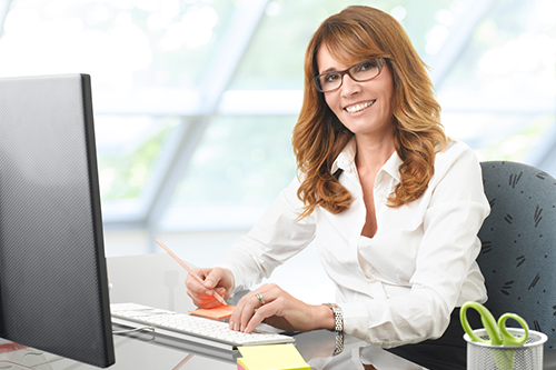 An executive assistant sits smiling at her desk