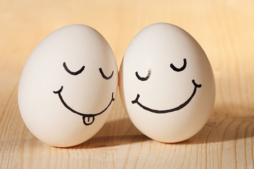 Two eggs are leaning against each other with smiling faces drawn on them
