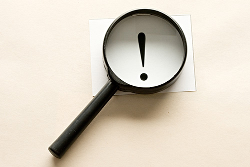 A magnifying glass shows an exclamation point