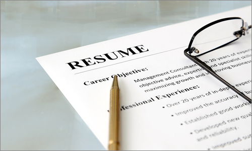 Glasses and a pencil lie on a resume