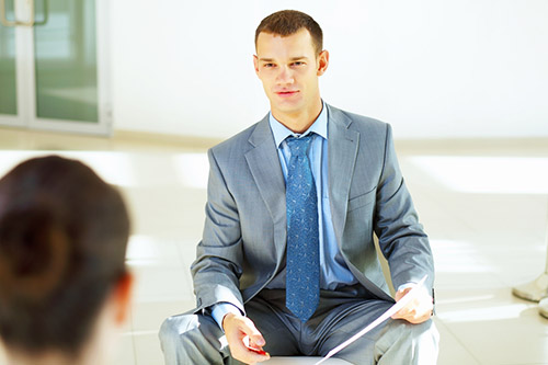 A prospect listens to an explanation of company benefits during an interview