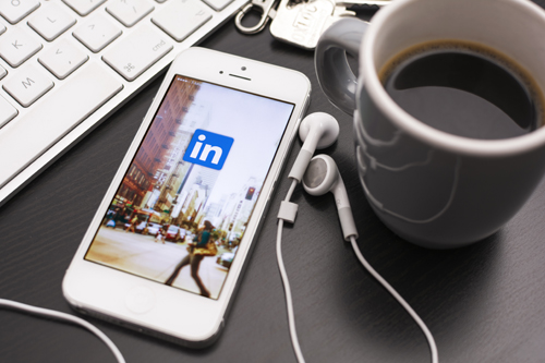 A keyboard, a set of keys, a cup of coffee, ear buds and a smartphone with a LinkedIn page on the screen sit on a desk