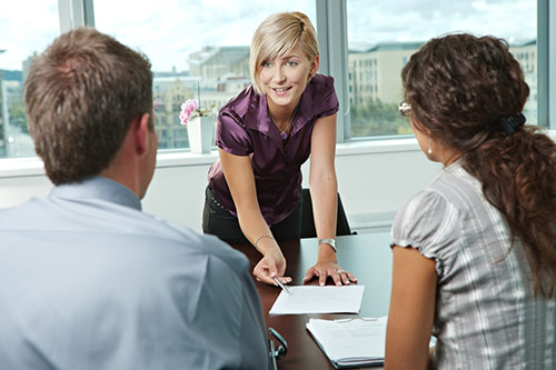 A recruiter talks to two candidates about working for a staffing agency