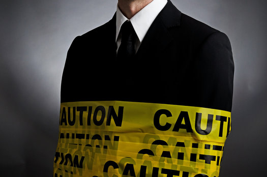A professional is wrapped in caution tape to warn hiring managers against making a bad hire