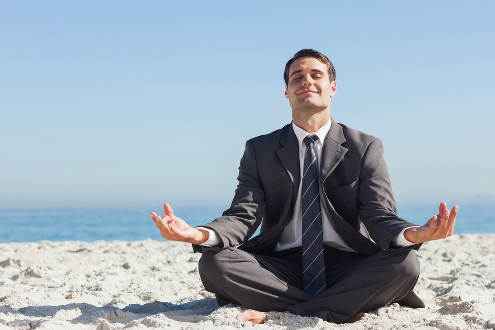 A man in a suit strikes a yoga pose on the beach in search of work-life balance