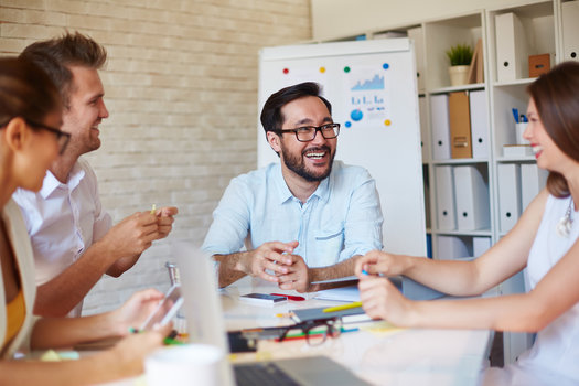 Happy employees are gathered around a conference table at a company that has an effective employee retention program
