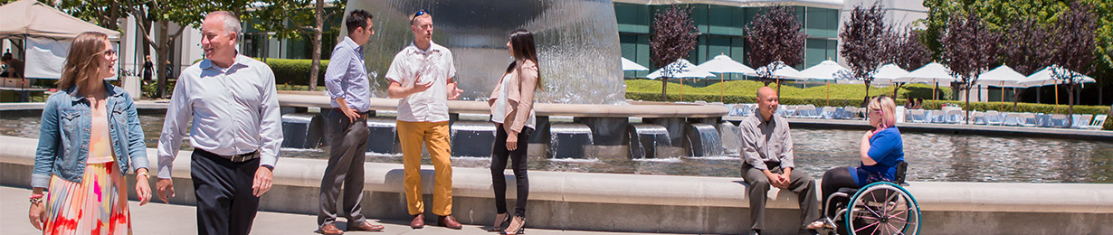 Robert Half employees casually converse by a fountain outside the office