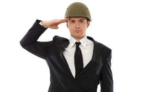 A military veteran wearing a business suit and helmet, salutes the camera