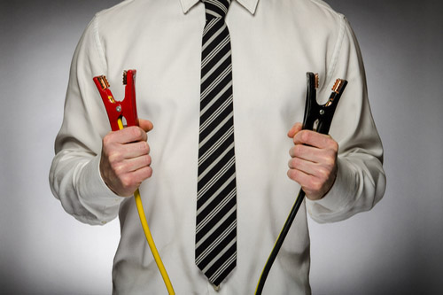 A businessman holds up the clamps of a set of auto battery jumper cables