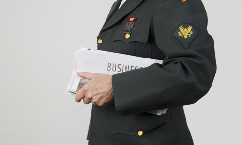 A military person holds a business newspaper